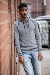 A young, hip, black man poses against a brick wall in NYC