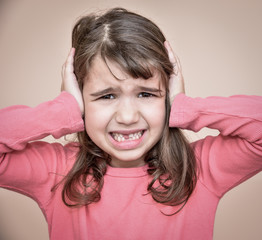 Toothless young girl covering her ears with hands