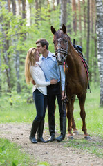 Young couple enjoying horseback riding.