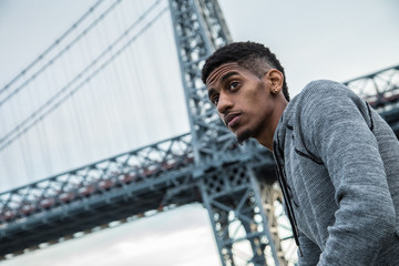 A portrait of a young, black man along NYC's East River Williamsburg Bridge