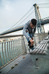A young man cleans his Timberlands infront of the Williamsburg Bridge