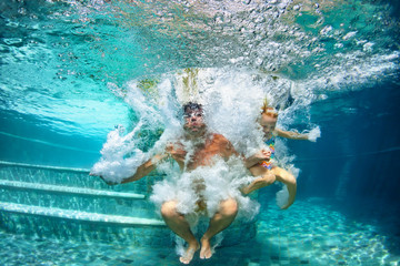 Happy family - father, baby daughter swim and dive in swimming pool with fun - jump deep down underwater with splashes. Lifestyle, summer children water sport activity and swimming lessons with parent