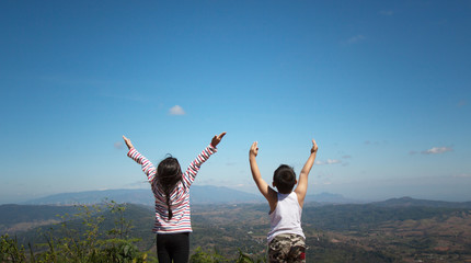 Two little children raise their arms up to the sky. They feel free