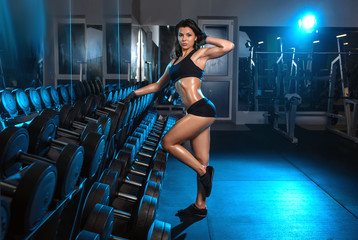 athletic woman workout with dumbbells at gym background