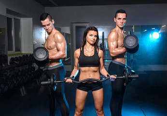 Friends in gym together workout with fitness equipment. Man holding dumbbell workout at gym. Group people working strong on body. Smiling woman on foreground.