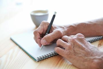 Male hands writing in copybook, closeup