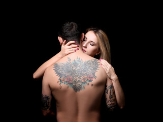 Sexy woman hugging tattooed man on black background