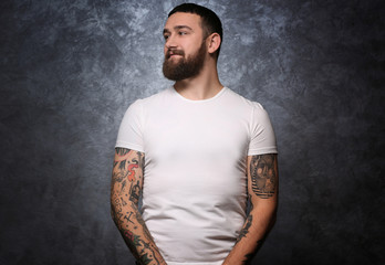 Portrait of tattooed man on gray background