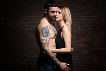 Fashion tattooed  couple on brick wall background