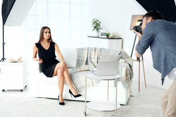 Young beautiful model posing on sofa in professional photo studio