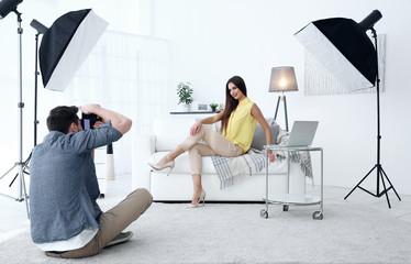 Young beautiful model posing on sofa in professional photo studio