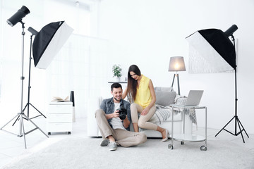 Photographer and model in professional studio discussing picture on camera display