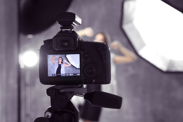 Picture of young beautiful model on camera display while shooting