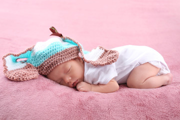 Cute little baby with wicker cap sleeping on bed at home