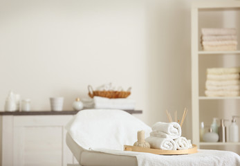 Couch with towels and herbal bags in spa salon