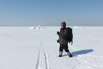 Nordic Walking - adult man with a backpack hiking  on snow in winter