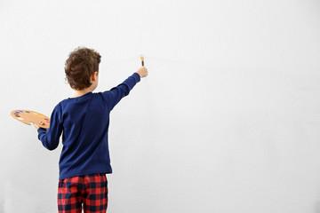 Cute little boy painting on light wall