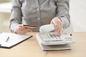 Woman with bank card calling the clients support center while sitting in office
