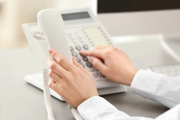 Hands of woman dialing number on telephone in office