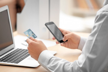 Man sitting in office with credit card and mobile phone