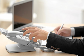 Man picking up telephone receiver while working in office