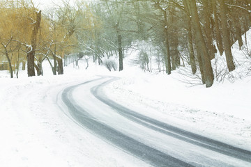 Traces of tires on snow covered road bend in winter time