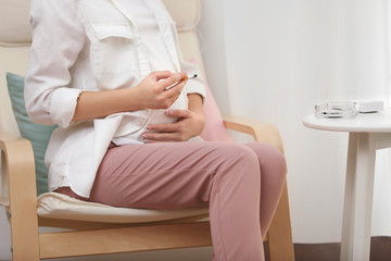 Smoking pregnant woman sitting on chair
