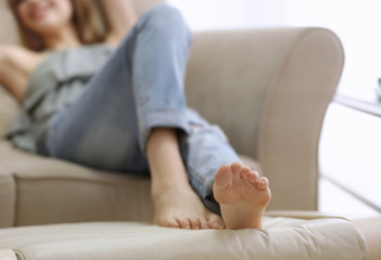 Feet of beautiful young woman resting at home, closeup