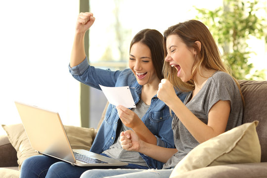 Excited roommates reading a bank notification