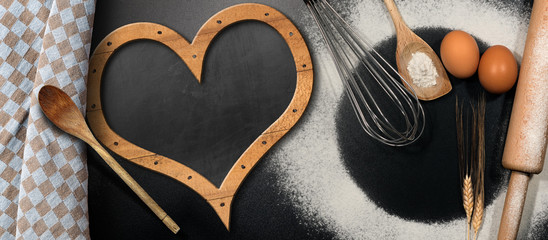 Baking background with empty blackboard in the shape of a heart, flour, eggs and kitchen utensils