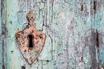 Old rusty metal lock and keyhole on a old turquoise wooden door as a vintage background
