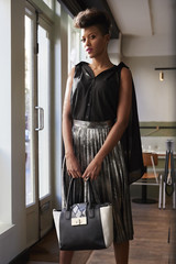 Chic woman holding handbag stands in cafe looking at camera