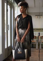 Fashionable woman holding handbag stands in cafe looking away