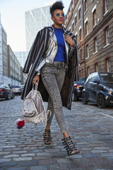 Woman in striped coat walking in street holding backpack
