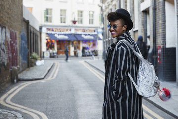 Woman in striped coat and hat turns and smiles in the street