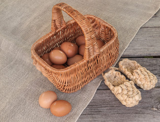 Rustic still life with basket with eggs and bast shoes