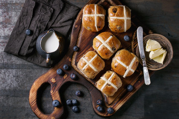 Hot cross buns on wooden cutting board served with butter, knife, fresh blueberries and jug of cream on textile papkin over old texture metal background. Top view, space. Easter baking.