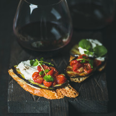 Wine and snack set. Brushetta with roasted eggplant, cherry tomatoes, garlic, cream cheese, arugula and glass of red wine on wooden board over dark background, selective focus, square crop. Slow food