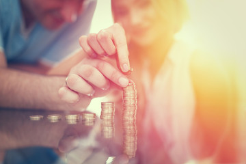 Young couple building money column from coins in sunset