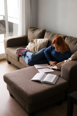 Woman with book taking notes