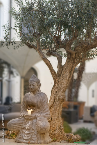 buddha statue mit kerze unter baum stockfotos und lizenzfreie bilder auf bild. Black Bedroom Furniture Sets. Home Design Ideas