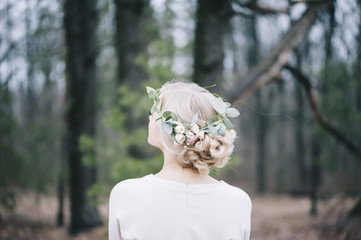 Beautiful blond bride with a floral head band standing back to the camera in the winter forest