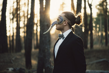 Mysterious handsome groom in a traditional venetian mask, wearing a suit in the Autumn forest
