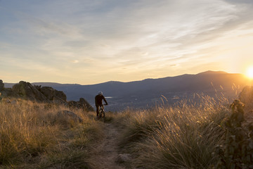 Cyclist on the mountain at sunset