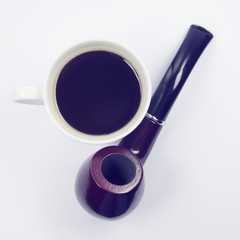 red wooden pipe and cup of coffee