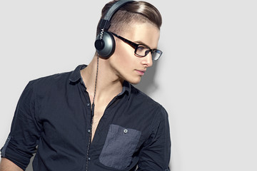 Handsome young man enjoying music on headphones over gray background