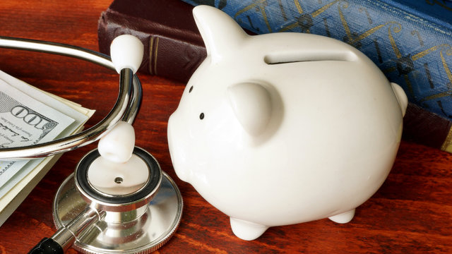 Stethoscope, piggy bank and cash. Affordable health care concept.