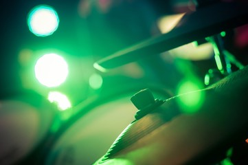 Electronic drum set with cymbals and blurred stage lights on a background