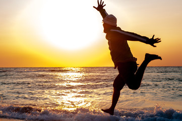 A man jumps joyfully against the sea
