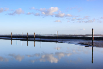 Calm sea, blue sky and wooden poles